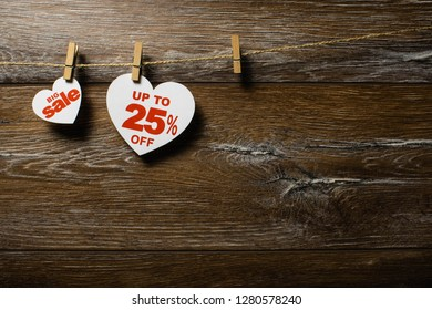 White hearts and discounts with romantic pattern on wooden background. Hearts of 25 % hanging on rope by clothespins