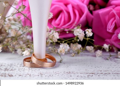 White heels, pair of engagement rings and bouquet of pink roses on white table. Wedding composition
