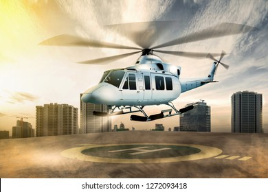 White helicopter landing on helipad at building rooftop with cityscapes background