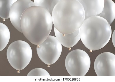 white helium balloons on beige grey background