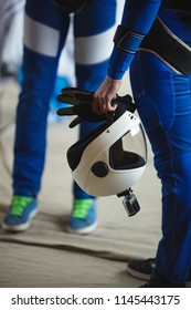 White helmet and gloves in a skydiver hand close-up. Parachute equipment.