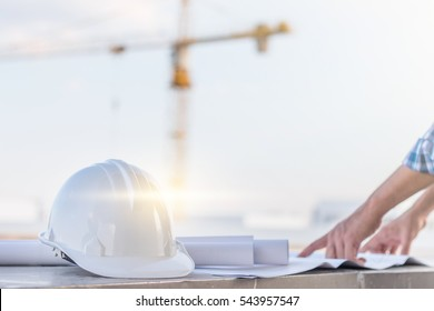 The white helmet and the man verify blueprint for his project with construction site and crane background