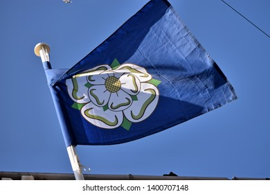 The white heraldic rose of the house of York on a flag welcoming the Tour de Yorkshire cycling race to the village of Kippax, Leeds, Yorkshire, England, UK, May 3rd 2019.