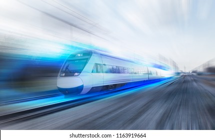 White high speed train runs on rail tracks . Train in motion.