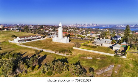 White historic Macquarie lighthouse on elevated South Head headland overlooking Watsons bay eastern suburb in Sydney with city CBD and harbour in background.