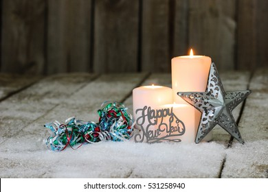 White holiday candles burning by silver tin star, Happy New Year and colorful ribbon on snowy rustic wooden background; holiday background with white copy space