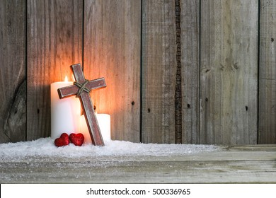 White holiday candles glowing behind wooden cross with red hearts in snow by antique rustic wood background; Christmas, Easter and religious background with copy space