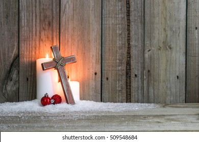 White holiday candles glowing behind wooden cross with red Christmas ornaments in snow by antique rustic wood background; Christmas and religious background with copy space