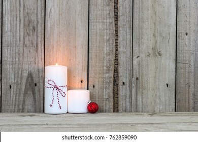 White holiday candles with red Christmas ornament by antique rustic wood background; home and spiritual background with copy space