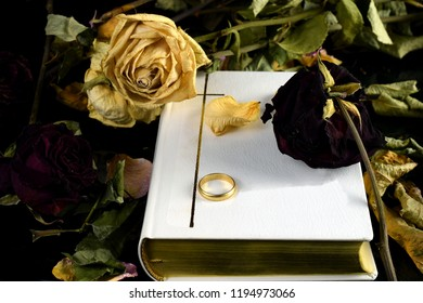 """White Holy Bible, one wedding ring and dry roses. Touching conceptual image of marriage, death and """"till death do us part"""" wedding vow."""
