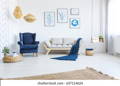 White home interior with sofa, armchair, posters, lamps and rug