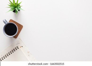 White home office desk. Copy space. Office stuff. Notebook, succulent, gray mug with coffee. Place for text. View from above.