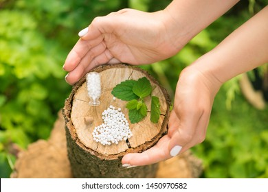 White homeopathic globules  in the form of a heart and green leaf mint in a wood stump. Treatment by alternative methods. Healthy lifestyle.