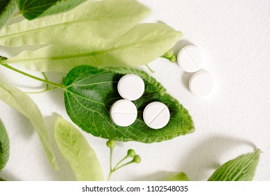 White homeopathic tablets, green kidney leaves and linden flowers. a medicinal plant, natural treatment with nature.