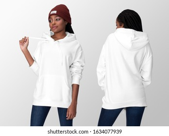 White hoodie on a young african american woman in jeans and hat, front and back, isolated, mockup template
