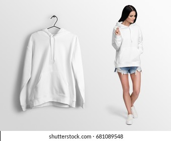 White hoodie on a young woman in shorts, isolated, mockup. Hanging hoodie, against empty wall background.