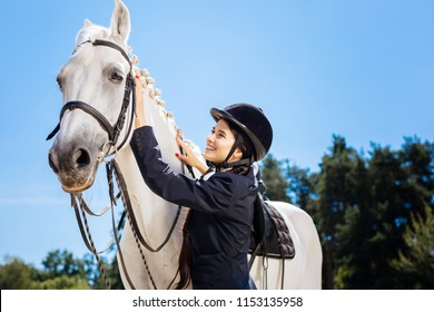 White horse. Appealing dark-haired horsewoman smiling broadly while looking at her gentle white horse