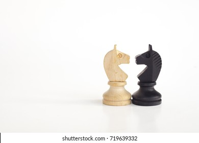 White horse and black horse, traditionally confronted in chess game, have reconciled. Image in isolated white background.