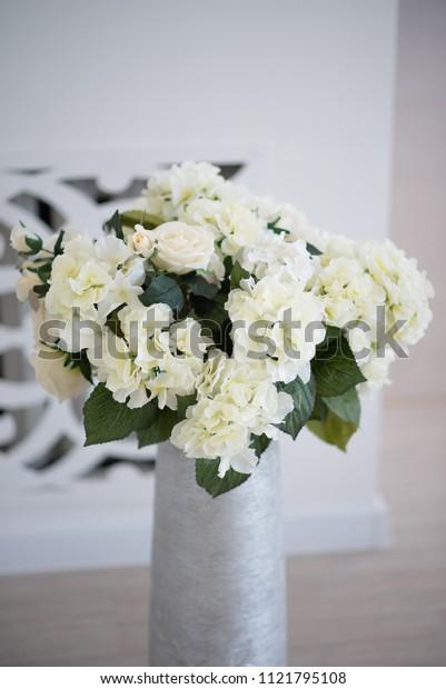 White hortensia bouquet in a high grey vase