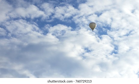 White hot air balloon on a cloudy sky, background, copy space.