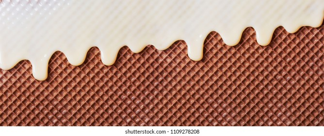 White hot chocolate on the wafer. Waffle covered with condensed milk close-up. White hot chocolate spreads on the wafer.