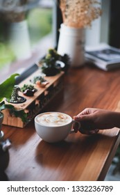 white hot coffee cup on wood table.woman hand holding coffee cup.