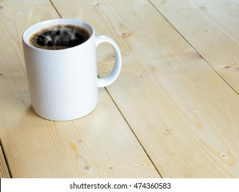 White hot mug or coffee cup with stream on wood table