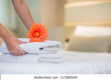 white hotel bed sheets and towel set with flower. maid cleaning bed. Room service