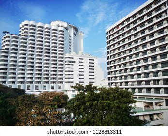 White hotel building with green trees against blue sky with clouds