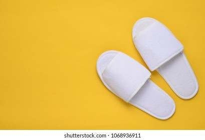 White hotel slippers on a yellow background, top view, minimalist trend