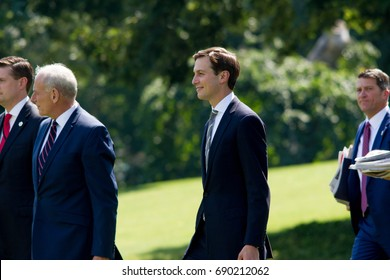 White House aide and Donald Trump's son-in-law, Jared Kushner (center), walks on to the South Lawn of the White House to board Marine One, Friday, August 4, 2017.