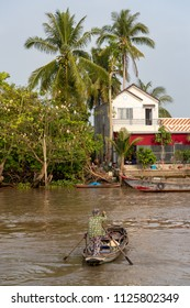 White house among the palm trees near the Mekong River in Vietnam