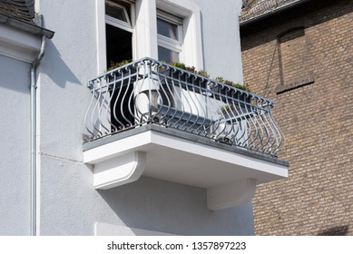 white house with a balcony and curved metal railing