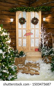 White house door decorated for christmas with xmas tree near and cozy bench near it