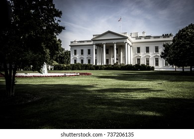 The White House - The front of The White House with blue cloudy sky and partly shaded grass from the trees. Taken from a low perspective.