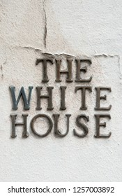 The White House in Mismatched Metal Letters Against a Cracked White Wall