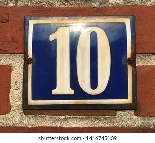 White house number 10 on a blue background, affixed to a red brick wall (early twentieth century). Tonning, Schleswig-Holstein, Germany