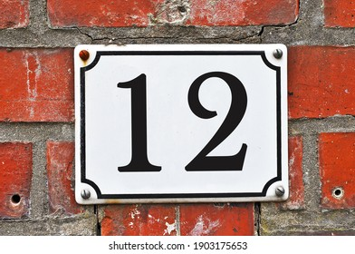 A white house number plaque, showing the number twelve (12)
