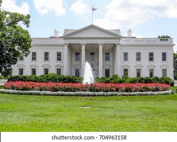 White House on blue background with green grass and clouds