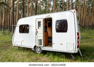White house on wheels standing on green grass in pinetree forest during summer travel