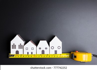 White house toy and construction tools on black background with copy space.Real estate concept, New house concept, Finance loan business concept, Repair maintenance concept