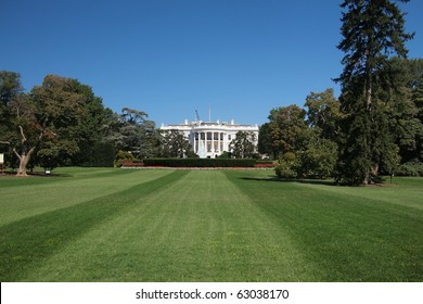 The White House in Washington DC with green lawn and beautiful blue sky
