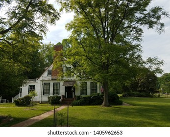 white house with windows and red chimney and green grass