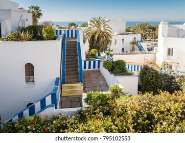 White houses in Agadir, Morocco with blue and white striped rail