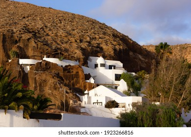 White houses embed in rocky mountain at sunset in Lanzarote island, Spain