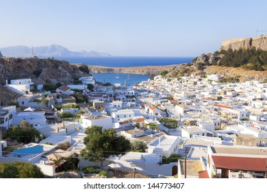 White houses of the village of Lindos, a fortress on the hill and the beautiful bay.