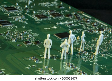 white human dolls on electric circuit board, people and electronics concept