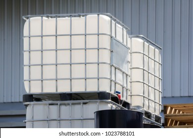 white ibc container in outdoor stock yard of factory, white plastic chemical tanks
