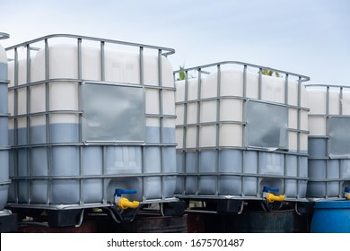 white ibc container in outdoor stock yard of factory, white plastic chemical tanks.