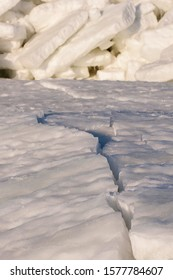 White ice with crack gap flaw rift and stack on frozen sea in bright sunny cold winter day light with shadows